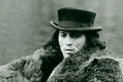 Johnny Depp, wearing a bear skin coat and John Bull Topper hat, stares out with a glazed look]