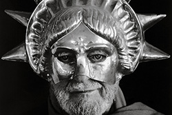 [black and white image of bearded man wearing a partial Statue of Liberty mask]