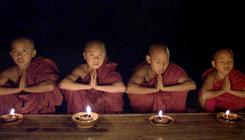 [four young monks in dark red robes sit behind a low wooden table with a burning lamp in front of each of them]
