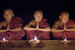 [three young monks in dark red robes sit behind a low wooden table with a burning lamp in front of each of them]