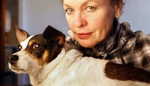 [white woman looks to camera holding a brown and white dog with gentle eyes]