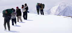 [a bright mountainous deep snow covered landscape with seven people trudging across in a single line]