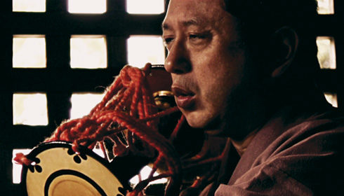 [Japanese man vocalizes while holding instrument tied with red cord]
