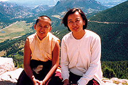 [two smiling women, one with shaved head, sit side by side on a stone wall with mountainous landscape behind them]