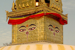 [gold covered stupa with painted face on each side of top, draped with red and gold banner]