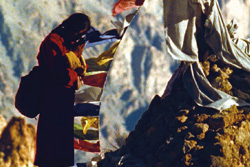 [a man in red robe stands with hands clasped amidst prayer flags]