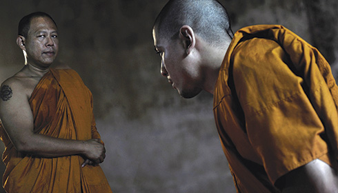[younger Thai monk bows to senior monk]