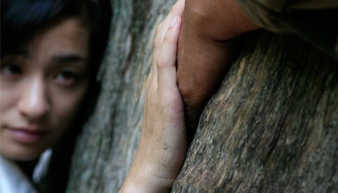 [leaning on a tree trunk, a Japanese woman's face gazes at her hand clasping a man's hand]