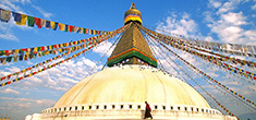 [dark red robed monk circumambulates a prayer flag draped domed stupa against blue sky with clouds]