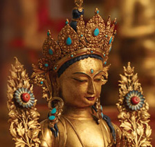 [head and shoulders of golden tara statue with turquoise and coral]