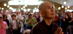 [asian man in brown tunic with shaved head and clasped hands gazes upward with a crowd of people and white lights behind him]