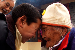 [young Tibetan boy and old Tibetan woman smile and press foreheads in greeting]