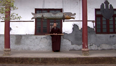 [monk in deep red robe stands against a windowed distressed wall, under a hanging wooden fish, holding a horizontal wooden stick]