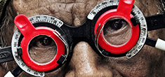 [close-up of older man wearing eye examination glasses with circular red inner frames]