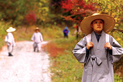 [Asian woman in grey robes and wide brimmed straw hat holds white shoulder straps while walking along a dirt road with autumn colored trees and two smaller figures in background]