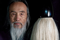 [close-up of white bearded Asian man against a dark background looking to camera with enormous white haired paint brush left of his head]