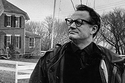 [[black and white image of man in dark framed glasses, dark shirt and jacket looks out frowning with house and grassy area, white fence, and flying flag in background]