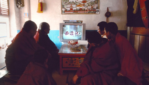 Monks and novices watch Chinese television in The Silent Holy Stones.