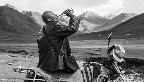 [black and white image of man with shaved head, wearing a dark leather jacket, and drinking from a bottle while sitting on a motorcycle with a mountainous landscape in the background]