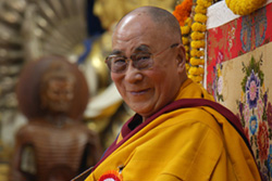 [smiling man with glasses, shaved head, and gold and maroon robes looks to camera while seated near a buddhist statue]