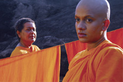 [two Sri Lankan nuns stand on either side of hanging wash]