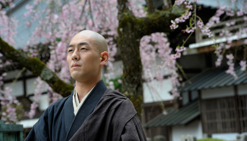 Zen monk Eihei Dogen standing in front of cherry blossoms in the film Zen.