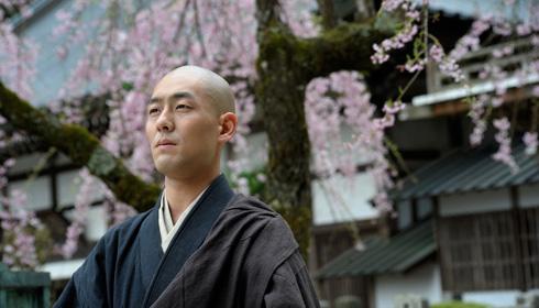 Kantarou Nakamura as Zen monk Eihei Dogen, standing in front of cherry blossoms